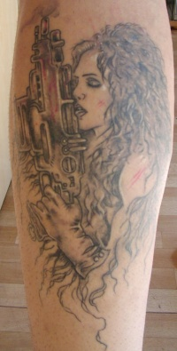 Tattoo of woman with long hear and shooter