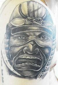 Warrior and small demon head on tattoo