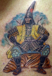 Japanese warrior sitting on rock tattoo