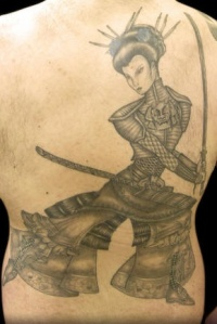 Black woman warrior tattoo on back